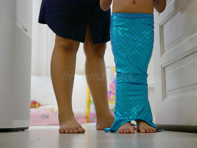 Little baby girl`s legs, with her mom`s help to get dressed, in a mermaid pants / costume at home stock photo