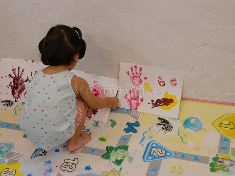 Little baby girl sitting and arraging her artworks at home - baby handprint / fingerprint painting. Little baby girl sitting and arraging her artworks at home by stock photo