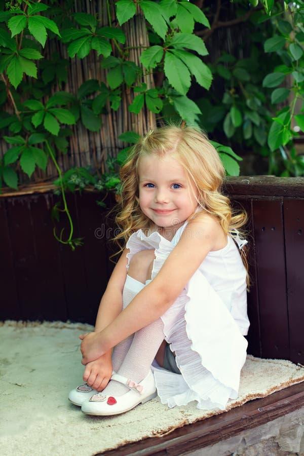 Little Baby Girl Sitting On Bench In Garden Stock Image