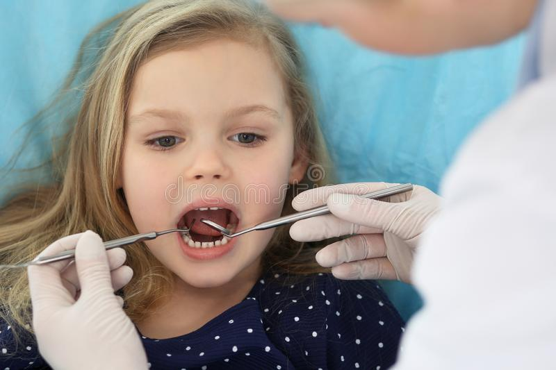 Little baby girl sitting at dental chair with open mouth and feeling fear during oral check up while doctor. Visiting royalty free stock images