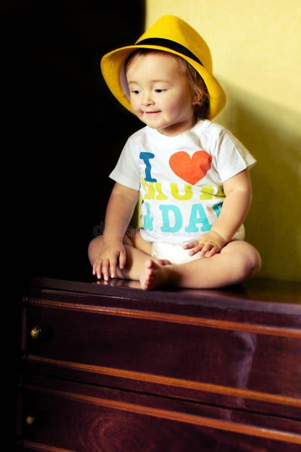 Little baby girl sitting on the dresser stock images