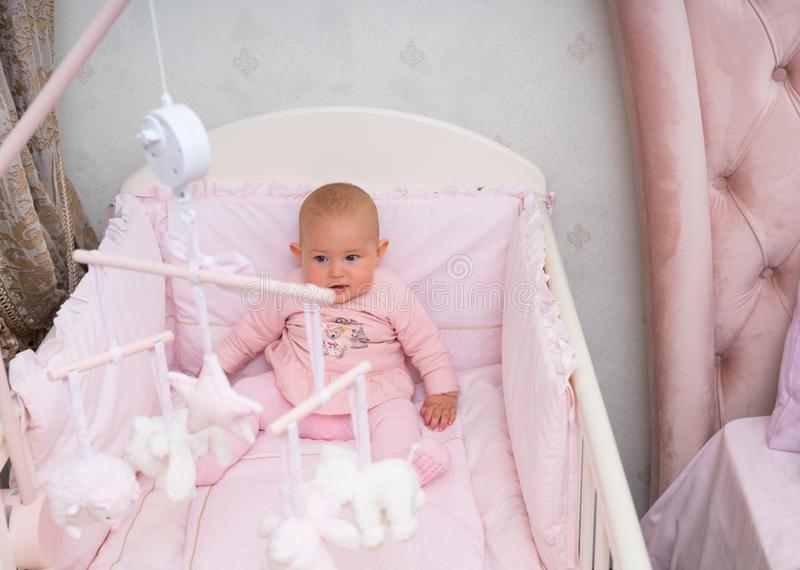 Little baby girl sitting in her crib. Little baby girl sitting in her crib watching a hanging mobile with little white toys above her head stock photos