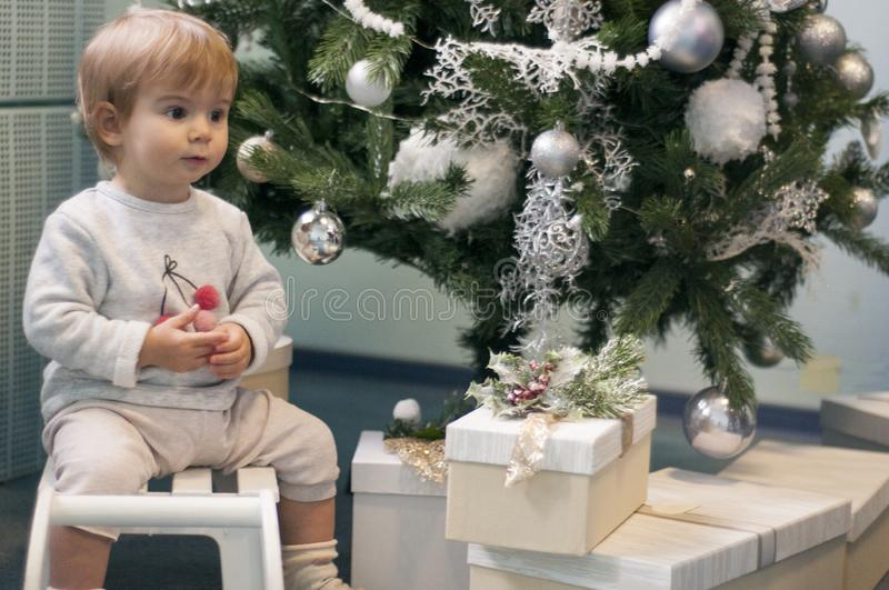 Little baby girl sitting on a toy sledge under Christmas tree with silver decorations and presents. Opening presents. stock images
