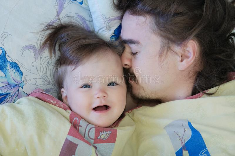 Little baby girl sleeping with dad in the morning. Happy family. royalty free stock photo