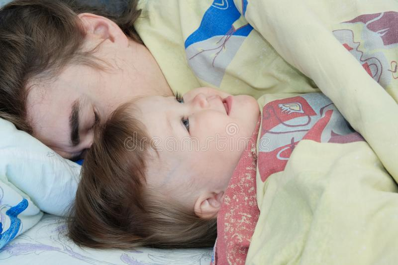 Little baby girl sleeping with dad in the morning. Happy parent. Happy family. stock photos