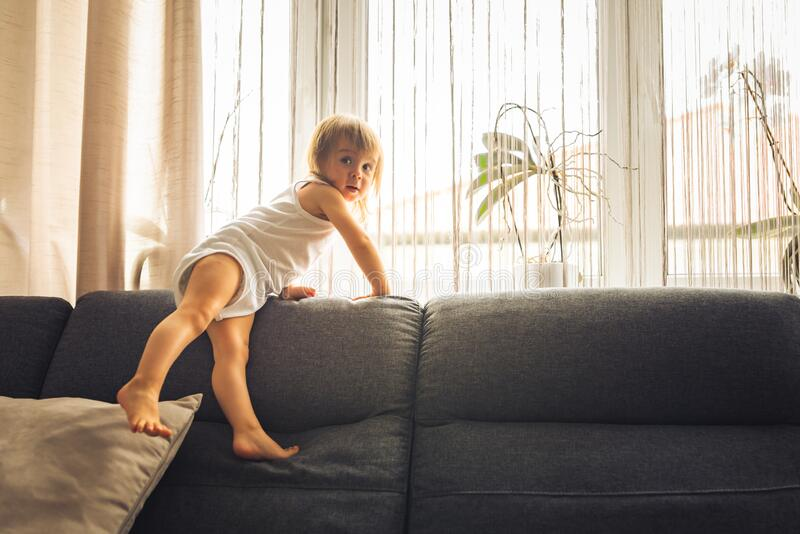 Little baby girl on the sofa at home. copy space royalty free stock photos