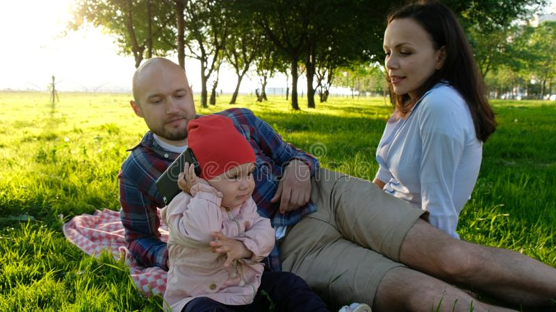 Little baby girl takes a smartphone and answers a phone call and talks close up. Happy family having a rest on a summer royalty free stock photo