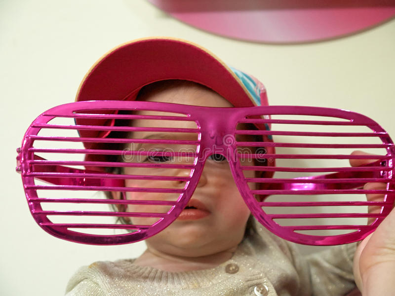 Little baby girl toddler in the big funny glasses royalty free stock photos