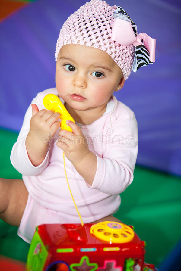 Little baby girl with a toy phone royalty free stock photo