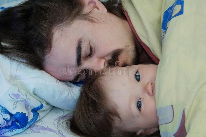Little baby girl wake up in the morning. Parent tired sleeping. Happy Father lying on bed stock image