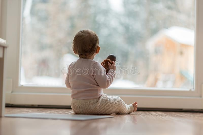 Little baby girl watching the snow outdoors royalty free stock image