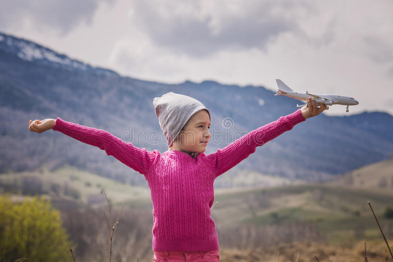 Little baby girl with white toy airplane in hands on a background of mountains stock image