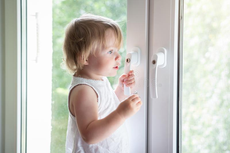 Little baby girl on window sill stock photography