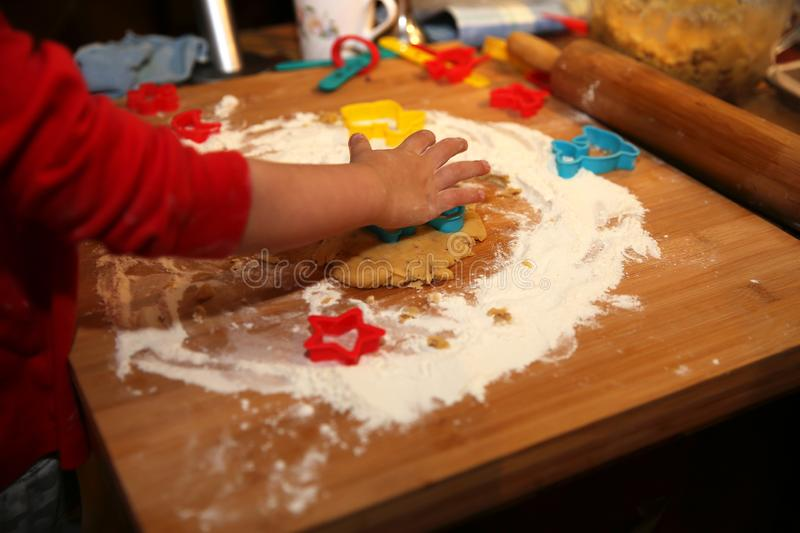 Little baby hand making cookies at home in the kitchen. Little baby hand making christmas cookies at home in the kitchen stock photos