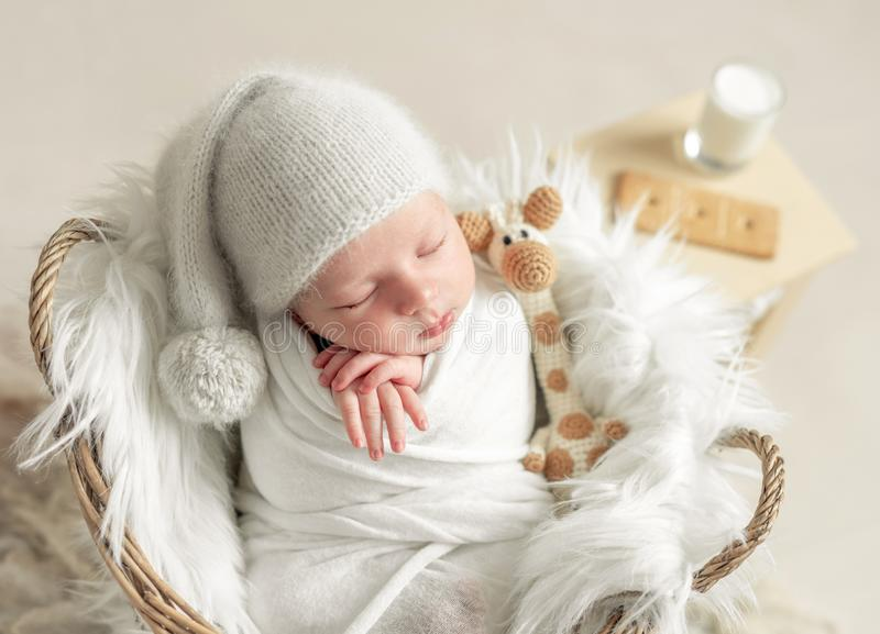 Little baby sleeping in basket with toy. Little baby in hat covered in white blanket sleeping in basket with toy royalty free stock photo