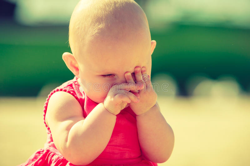 Little baby hiding face in hands. Little baby being shy and hiding face in hand on sunny day outdoor stock photos