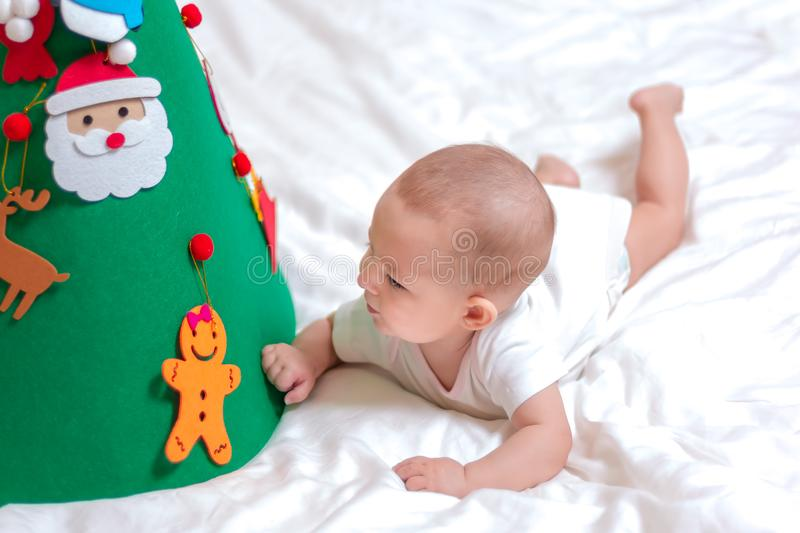 Little baby infant. Playing with a Christmas tree. lying on the bed. Surprisedly looks under the xmas tree. studies a toy spruce. On which toys hang royalty free stock image