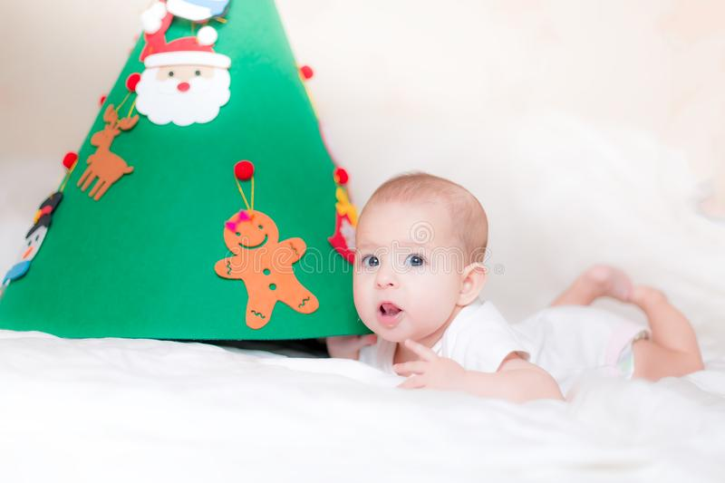 Little baby infant. Playing with a Christmas tree. lying on the bed. Surprisedly looks under the xmas tree. studies a toy spruce. On which toys hang stock photo