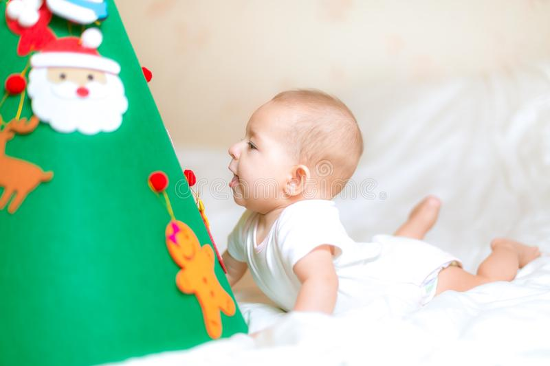 Little baby infant. Playing with a Christmas tree. lying on the bed. Surprisedly looks under the xmas tree. studies a toy spruce. On which toys hang royalty free stock images