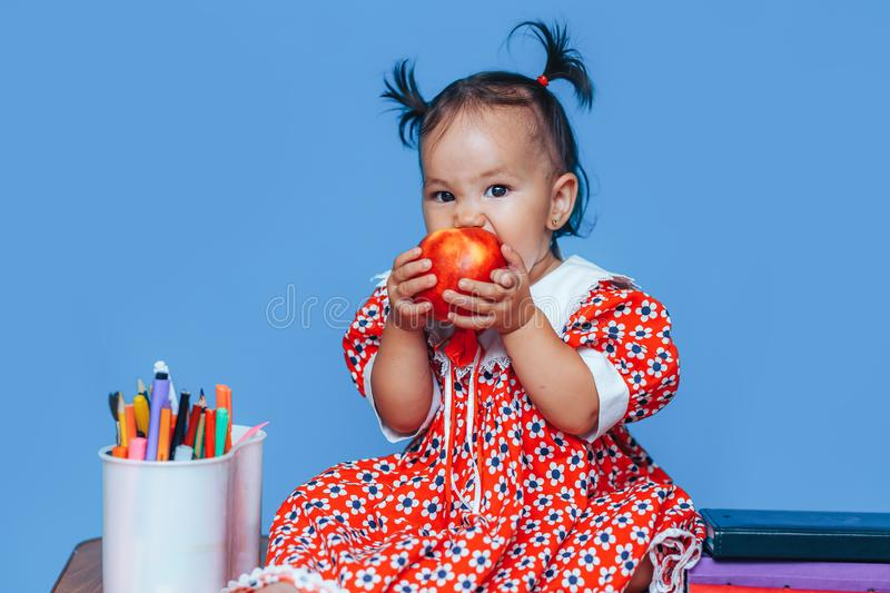 Little baby kazakh girl in red dress at the Desk eating apple.  royalty free stock image