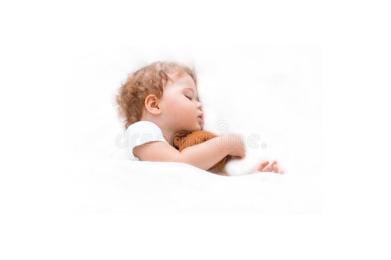 Little baby kid sleeps on a clean bedspread hugging a teddy bear. Caucasian child girl boy sitting dreams on big bed, white royalty free stock photos