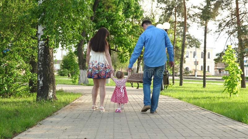Little baby learning how to walk with mom and dad,happy family walking in summer Park royalty free stock images