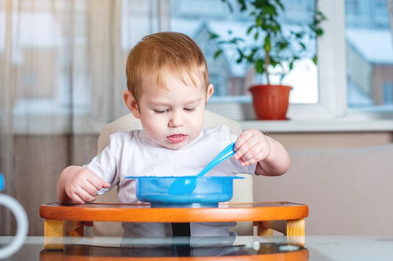 Little baby learning to eat with a spoon himself at the kids table in the kitchen. Healthy baby food. Little baby boy learning to eat with a spoon himself at the stock photo
