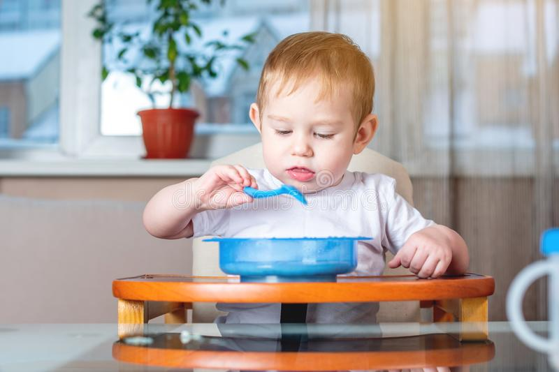 Little baby learning to eat with a spoon himself at the kids table in the kitchen. Healthy baby food. Little baby boy learning to eat with a spoon himself at the stock images