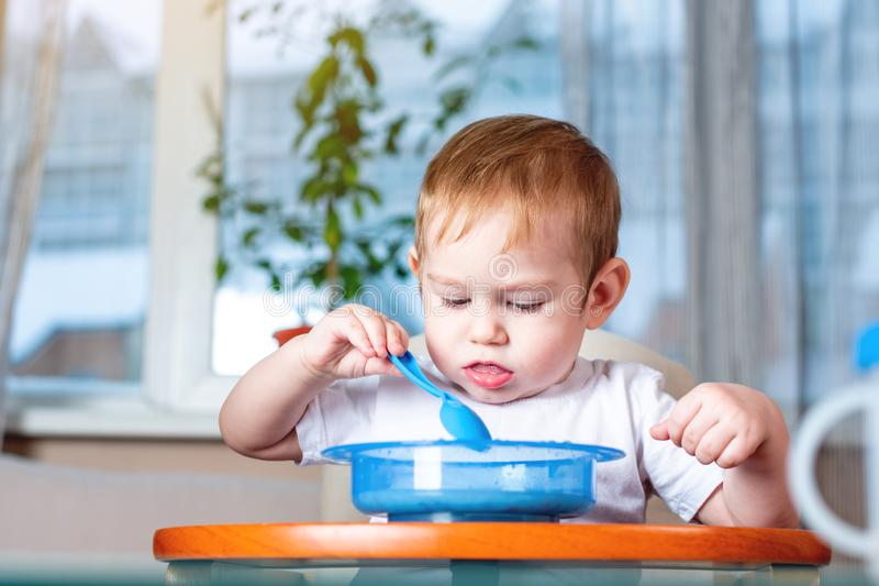 Little baby learning to eat with a spoon himself at the kids table in the kitchen. Healthy baby food. Little baby boy learning to eat with a spoon himself at the stock image