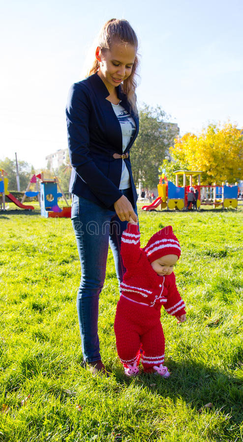 Little baby learning to walk. Mom holding baby's hand stock photography