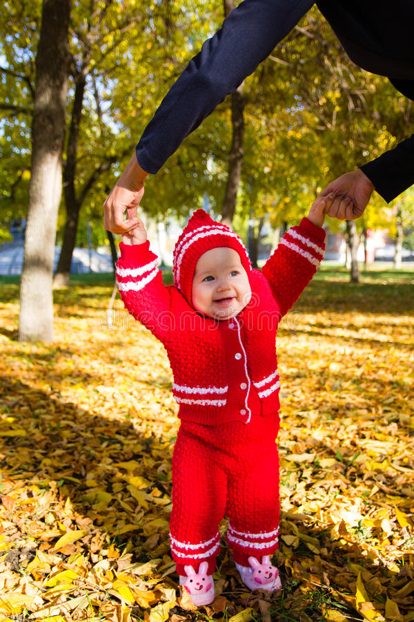 Little baby learning to walk. Mom holding the baby's hands royalty free stock image