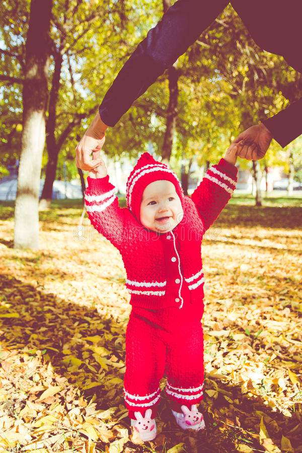 Little baby learning to walk. Mom holding the baby`s hands stock images