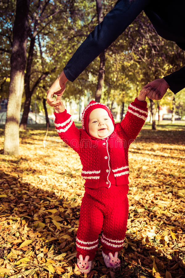 Little baby learning to walk. Mom holding the baby`s hands royalty free stock images