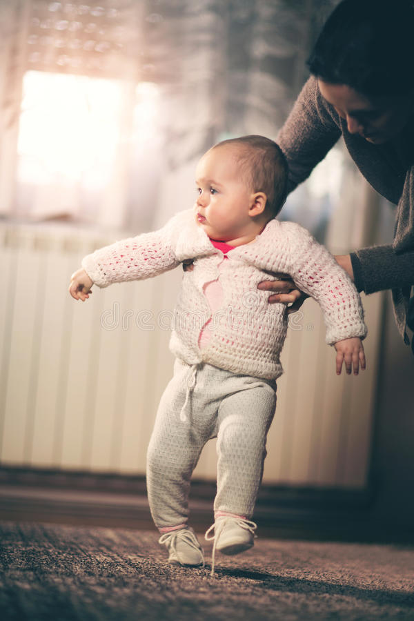 Little baby learning to walk with mother help at home stock images