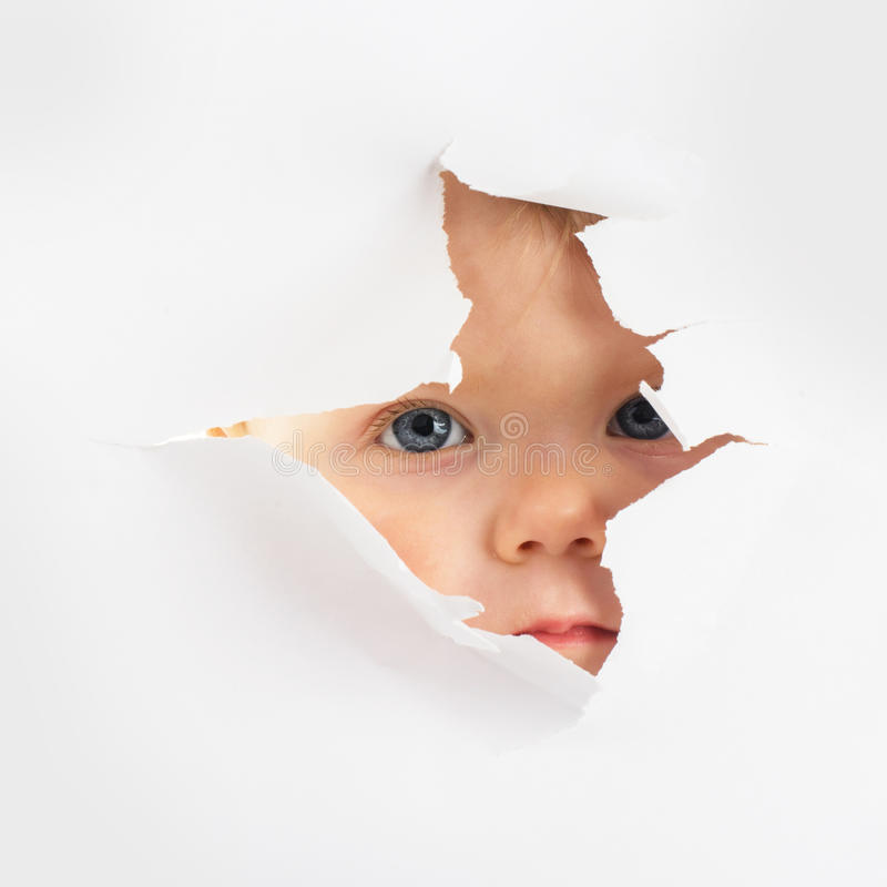 Little baby looking out of a hole royalty free stock photos