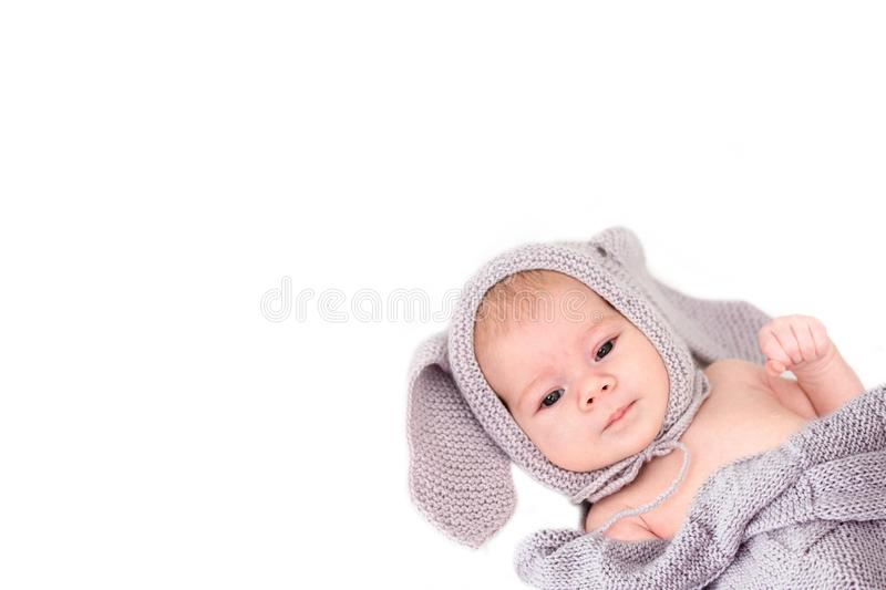 Little baby 3 months in a gray knitted hat with ears. White background, copy space. Portrait of Caucasian child, cute toddler stock photography