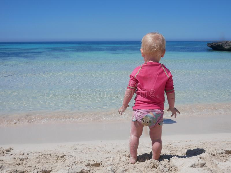 Little baby in pink swimming suit looking at the aquamarine blue see from a sand beach. Of Favignana island Sicily, Italy royalty free stock image