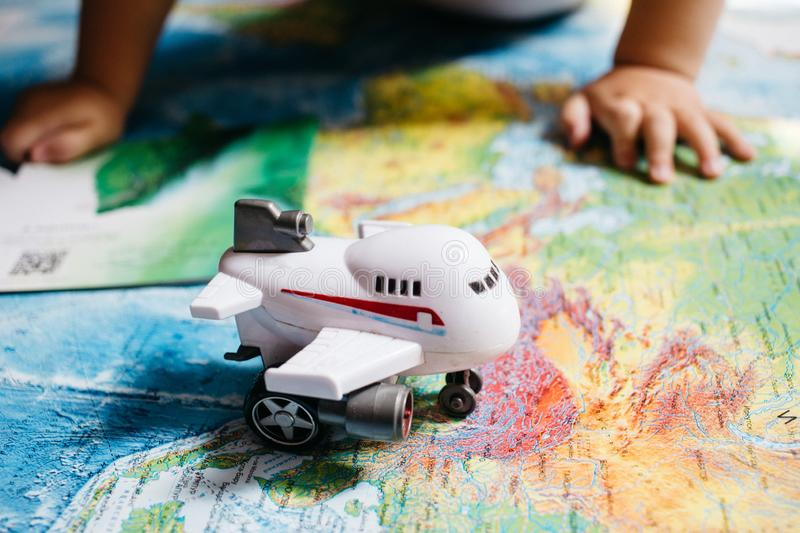 A little baby playing with an aircraft toy on the world map, childs hands, travel with children. A little baby playing with an aircraft toy on the world map stock image