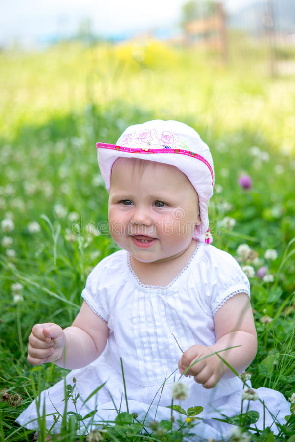 Little baby playing in the grass royalty free stock photography