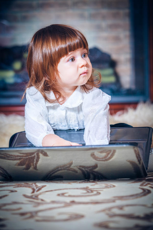 Little baby playing with laptop. On a carpet stock photo