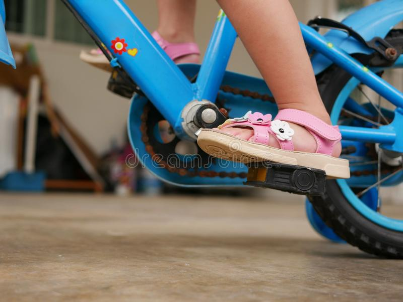 Little baby`s feet on pedals learning to ride a bicycle with training wheels stock photography