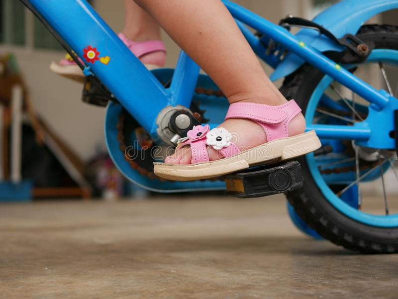 Little baby`s feet on pedals learning to ride a bicycle with training wheels stock photos