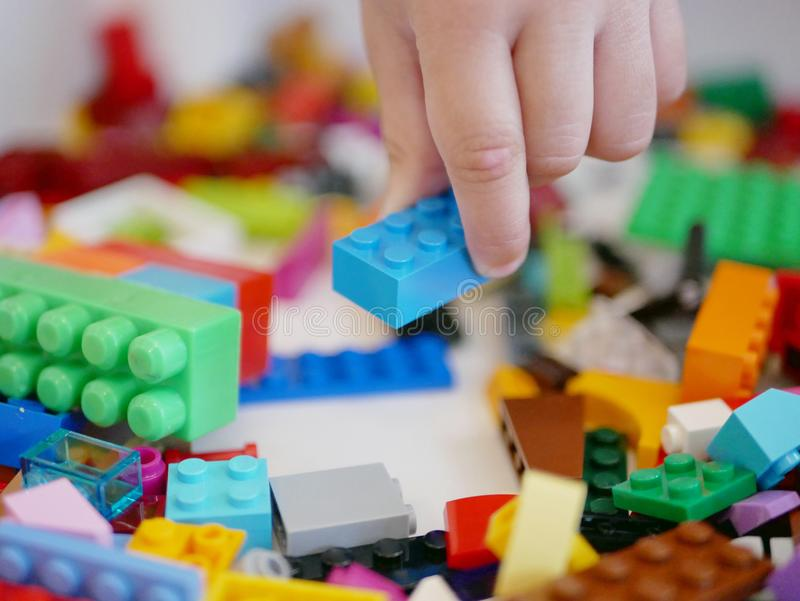 Little baby`s hand picking / choosing a piece of colorful interlocking plastic bricks. / blocks royalty free stock images