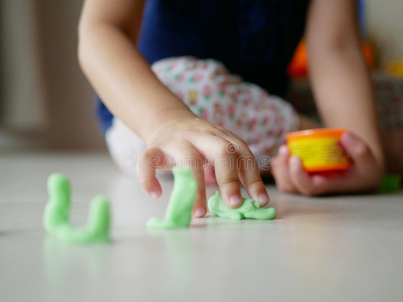 Little baby`s hand playing playdough on the house floor stock photo