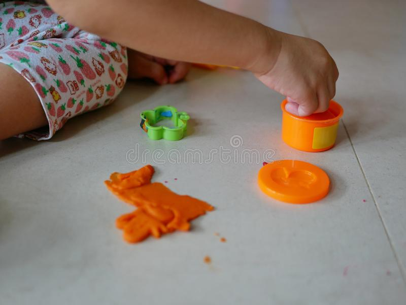 Little baby`s hands collecting and putting playdough back into the box, after finish playing. Allow baby to clean up their mess after playing helps create royalty free stock images