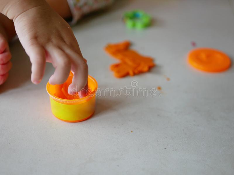 Little baby`s hand collecting and putting playdough back into the box, after finish playing. Allow baby to clean up their mess after playing helps create stock photos