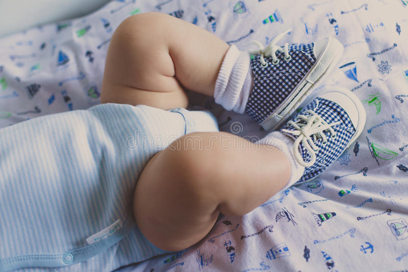Little baby shoes on his legs royalty free stock photo
