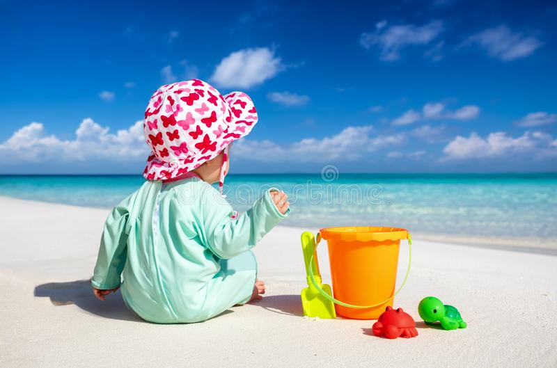 Little baby sits on a tropical beach and plays royalty free stock photo