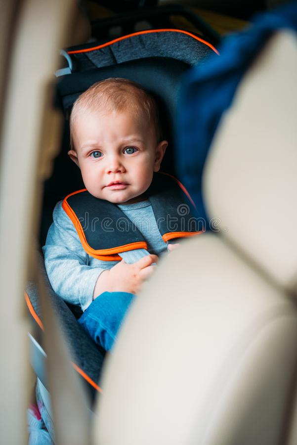 little baby sitting in child safety seat in car and looking royalty free stock photo