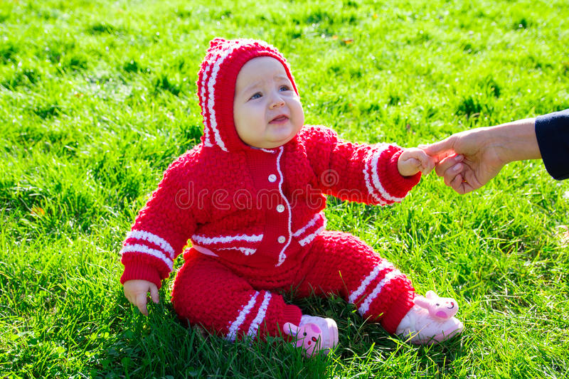 Little baby sitting on the grass. Mom holding the baby by the arm royalty free stock photos